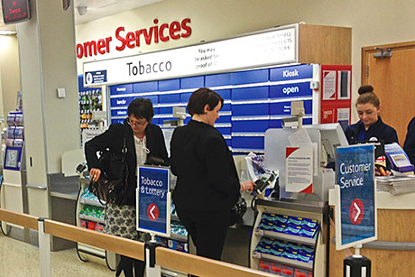 While the English version of the tobacco display ban (main picture above) allows a reasonable space to be displayed during transactions the Scottish system, now in supermarkets north of the border (inset picture), has led to kiosks being covered by potentially cumbersome systems of flaps.