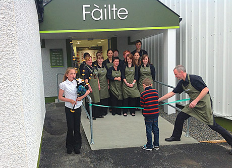 Ronald Maclennan, right, helps some very important people cut the ribbon at Maclennan's Supermarket on Benbecula.
