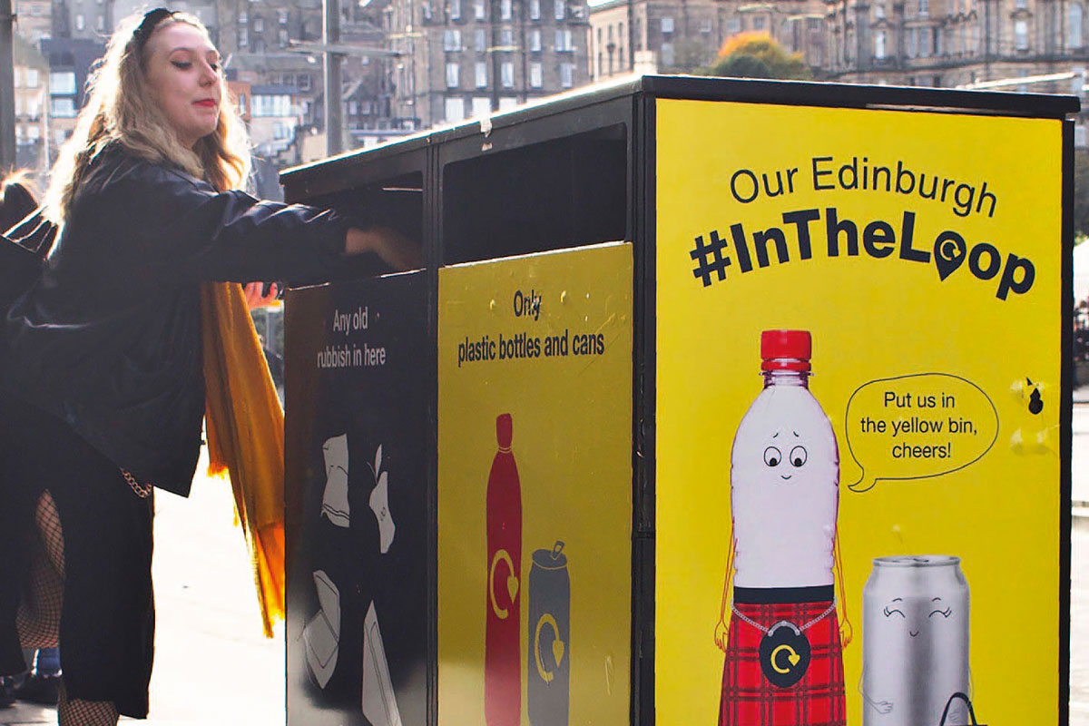 girl putting plastic bottle in recycling bin