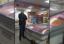 Shopkeeper infront of Freezers