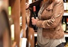 woman putting bottle in jacket
