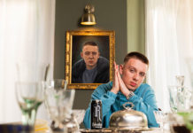 Man posing at dinner table with a can of Relentless