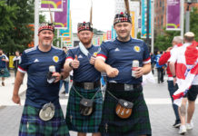 Men gathered in tartan kilts and Scottish Jerseys