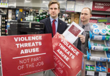 """Two men are holding red signs that read """"Violence threats abuse"""""""