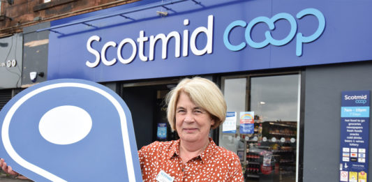 A woman standing outside Scotmid Coop Store Front
