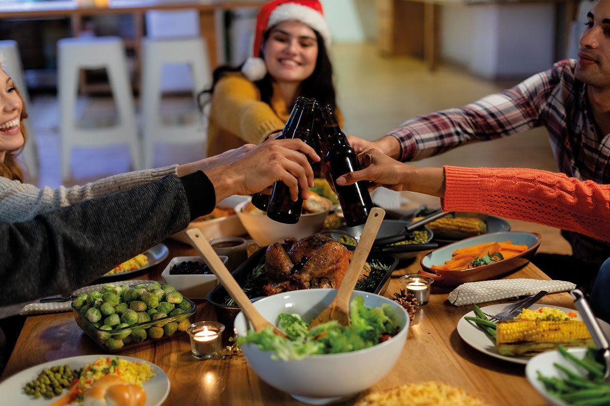Friends having Christmas dinner with bottles